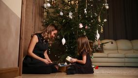 Mom and her daughter unleash the Christmas gift ribbons under the tree in the living room of their house.  stock video
