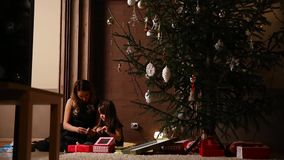 Mom and her daughter unleash the Christmas gift ribbons under the tree in the living room of their house.  stock video footage