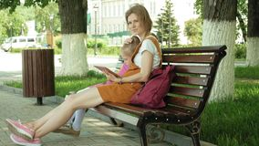 Mom and daughter use gadgets in the open air. Summer stock footage