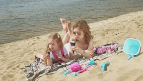 Mom and daughter on the river bank eat ice cream. Outdoor recreation. Mom with her daughter, a young woman in a white swimsuit and a little girl in pink clothes stock video