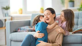 Mom and her daughters are playing. Mom and her daughters children girls are playing, smiling and hugging. Family holiday and togetherness stock photography