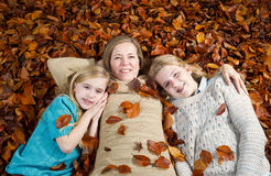 Mom and her daughters lying on a bed of leaves during the fall s Stock Photos