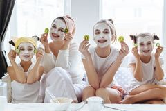 Mom with her daughters making clay face mask. Mother with children doing beauty treatment together. Morning skin care routine royalty free stock photography