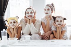 Mom with her daughters making clay face mask. Mother with children doing beauty treatment together. Morning skin care routine stock photo