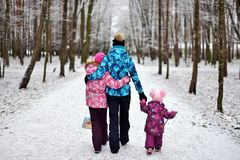 Mom and her daughters for a walk in the woods on a snowy winter stock photos