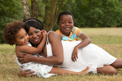 Mom and her dearest children. African mother and her kids are having fun in the nature stock images