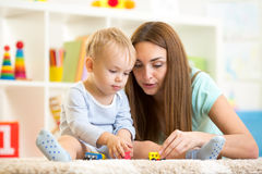 Mom with her kid son play together. Mom with kid son play together on floor in children room at home Stock Photo