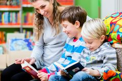 Mom with her kids for the first time in the library. Reading books Stock Photography