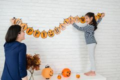 Mom and her kids hanging up the decoration. Happy family prepares for Halloween, Young mom and her kids hanging up the decoration celebrate the holidays Stock Images