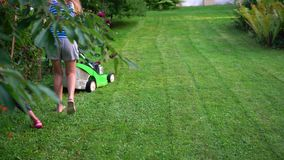 Mom with her little daughter child pushing lawn mower in evening garden stock video