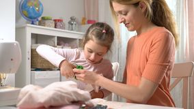 Mom and her little daughter do needlework together. Girl with scissors cuts the cloth for DIY. Children`s craft, education and training stock footage