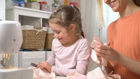 Mom and her little daughter do needlework together. Girl with scissors cuts the cloth for DIY. Children`s craft, education and training stock video footage