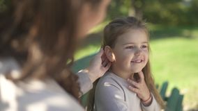 Mom and her little daughter are resting on a bench in the park stock video footage