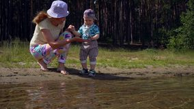 Mom and her little son play near the water on the shore of a forest lake on a summer sunny day. Mom and her child play on the shore of a forest lake, throw stock footage