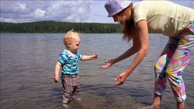 Mom and her little son play and splash around in the clear water of a forest lake on a sunny summer day against a blue sky stock footage