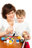 Mom with her son decorate Easter eggs Stock Photography