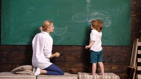 Mom and her son are drawing with chalk at school on green blackboard, rear view. Woman and boy draw. Back to school stock video footage