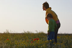 Mom and her son looking at the setting sun in spring steppe Royalty Free Stock Image