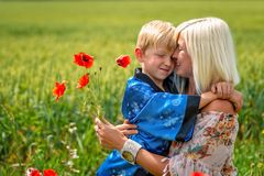 Mom with her son in a magnificent meadow. The boy embraces his mother tightly and lovingly stock image