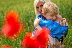 Mom with her son in a magnificent meadow. The boy embraces his mother tightly and lovingly stock images