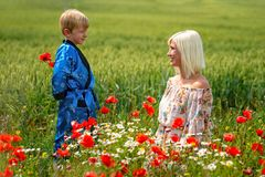 Mom with her son in a magnificent meadow. The boy surprised her mother with red poppies stock image