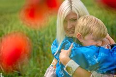 Mom with her son in a magnificent meadow. The boy embraces his mother tightly and lovingly royalty free stock photography