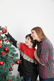 Mom with her son putting ornaments on the christmas tree Stock Images