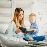 Mom and her Son Reading a Book. Happy Family at Home. Mom and her Son Reading a Book Stock Image