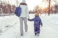 Mom with her son returned home after a walk in the park in the winter amid snow and snow drifts. Holding little boy by stock photography