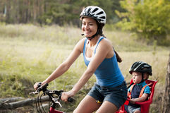 Mom with her son ride in the woods. Royalty Free Stock Photo