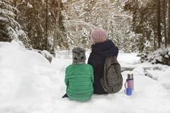 Mom with her son sitting and embracing in the background of snow-covered forest. Winter cloudy day. Back view royalty free stock photo