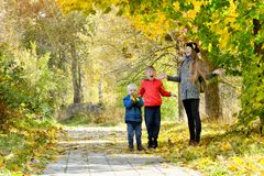 Mom and her sons toss the leaves. Autumn Park Royalty Free Stock Images