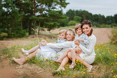 Mom and her three daughters hugging in a forest in summer.  Stock Images