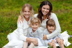 Mom and her three daughters hugging in a forest in summer.  Stock Photo