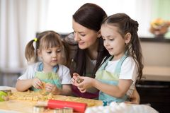 Mom with her 2 and 5 years old daughters are cooking in the kitchen to Mothers day royalty free stock photos