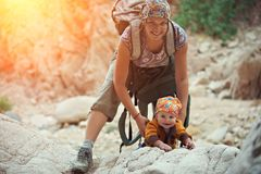 Mom and his little son are climbing in the canyon. Mom and his little son are traveling in the canyon Stock Photo