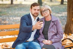 Mom and his son on a bench on a background of a blurred park background. Mom wearing glasses with his son in a suit, with a beard with a phone in his hand on a Stock Image