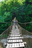 Mom and his son tourists cross the mountain river on suspension bridge Royalty Free Stock Image