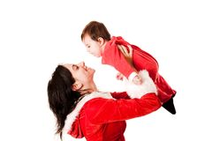 Mom holding her baby both dressed as Santa Stock Images