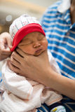 Mom holding newborn baby's in her hand. Asian mom holding newborn baby's head in her hands for belch after breastfeeding Stock Image