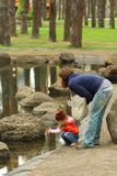 Mom holding toddler girl checking water in the spring park pond. Outdoors Royalty Free Stock Photos
