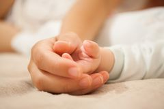 Mom holds the baby`s hand. Royalty Free Stock Photo