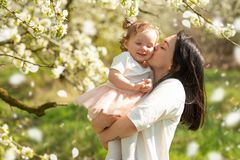 Mom holds the child in her arms in blooming gardens, Mother`s Day, March 8, spring mood. Horizontal photo royalty free stock image