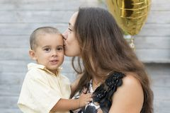 Mom holds a child in her arms and kisses him gently on the cheek. Mom gently kisses her son.  stock images