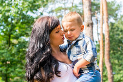 Mom holds in her arms and comforts her little boy who is crying,. In the park on a sunny day Stock Photography