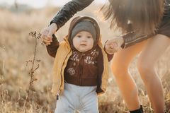 Mom holds her baby boy by the hands for a walk. Baby`s first steps. Mom holds her baby boy by the hands for a walk in the fall in nature. Baby`s first steps stock images