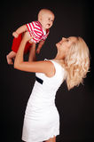 Mom holds her baby. Mother raising up of joyful baby boy in costume isolated on a dark background Stock Images