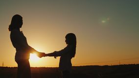 Mom holds her daughter`s hands, stand alone at sunset. Single parent concept