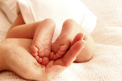 Mom holds the legs of cute newborn little baby Royalty Free Stock Photo
