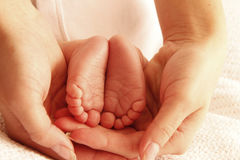Mom holds the legs of cute newborn little baby Royalty Free Stock Photography